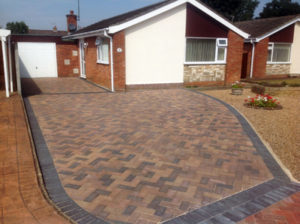 A sweeping Herringbone driveway with slab paving and gravel borders.